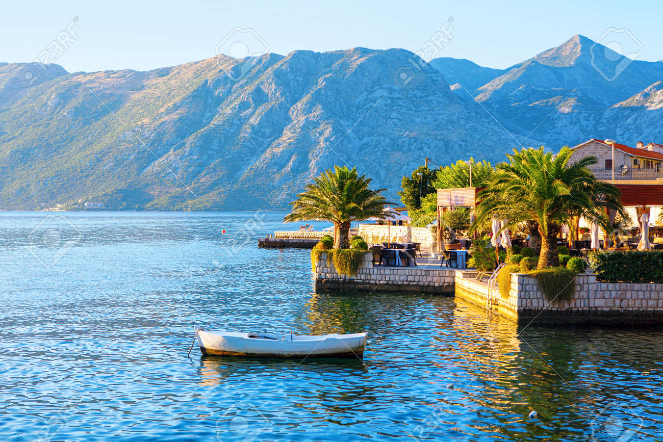 Coastal restaurant terrace at the tropical beach . Cafe terrace overlooking the Kotor Bay in Montenegro . Moored white boat - 169400074