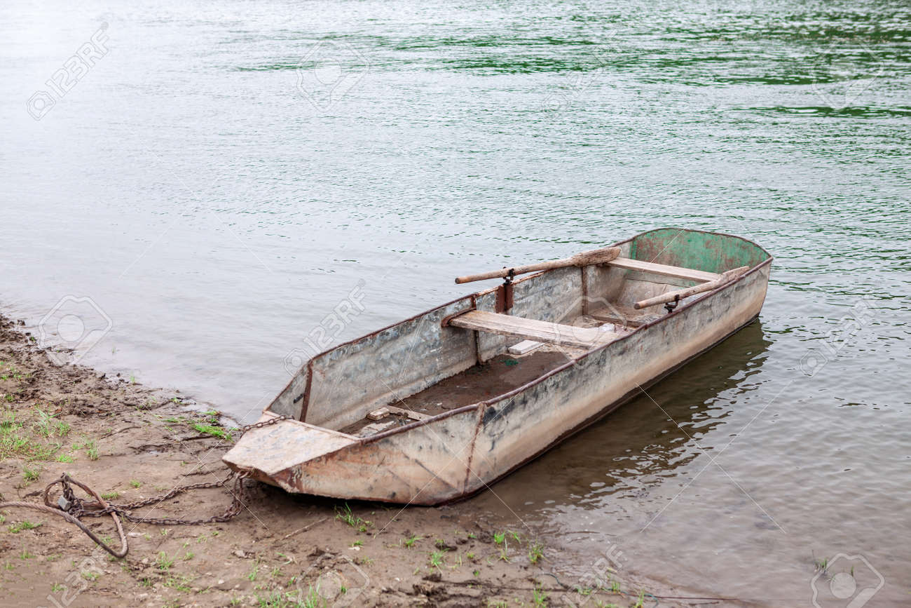 Moored rusty metal boat with oars . Fishing village - 169406724