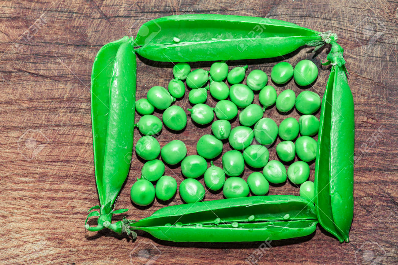 Green peas on the wooden table . Harvest of green peas - 169433774