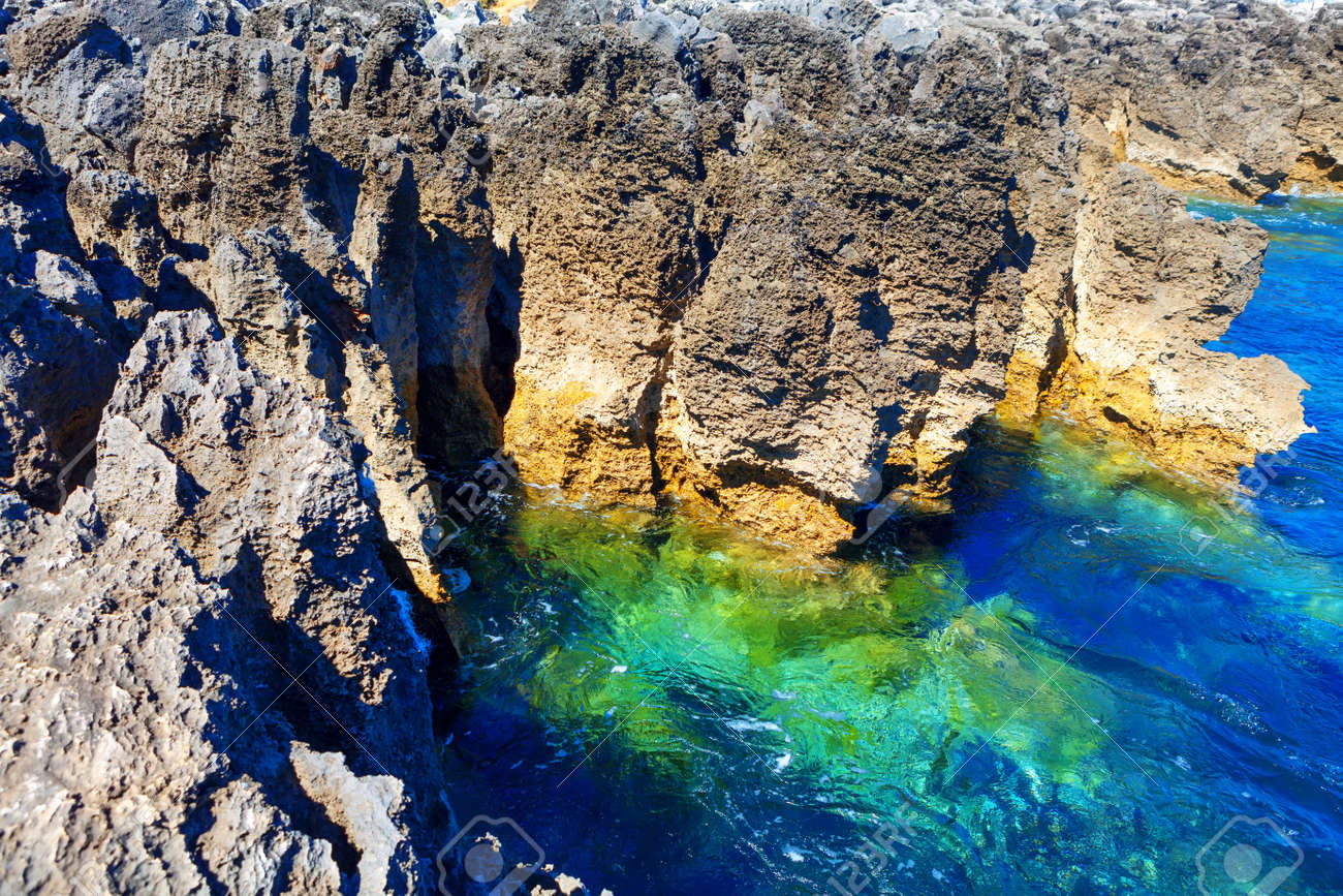 Coastal rock formation and ocean turquoise water . Tropical littoral . Oceanfront cliffs of Boca do Inferno - 170092780