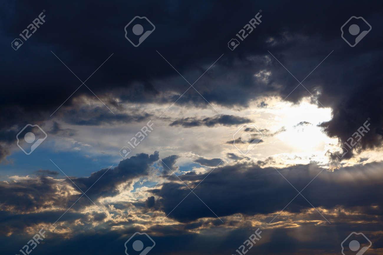 Sun shining through dark clouds . Sunlight rays and cloudy heaven - 169997071