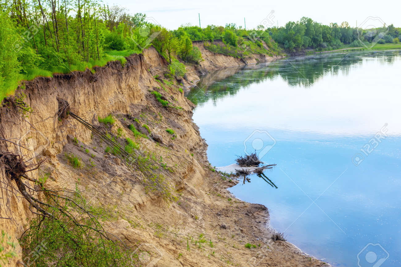 Riverside with clay cliff . Winding river scene . Exposed trees roots after a landslide - 169997185