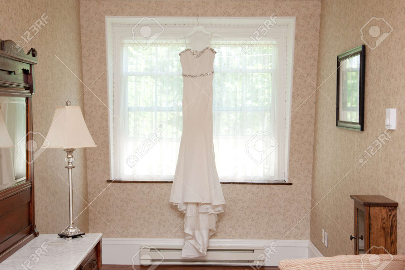 3fd3c4e9fc7b Archivio Fotografico - Un bellissimo abito da sposa slanciato è appeso alla  finestra di una vecchia stanza