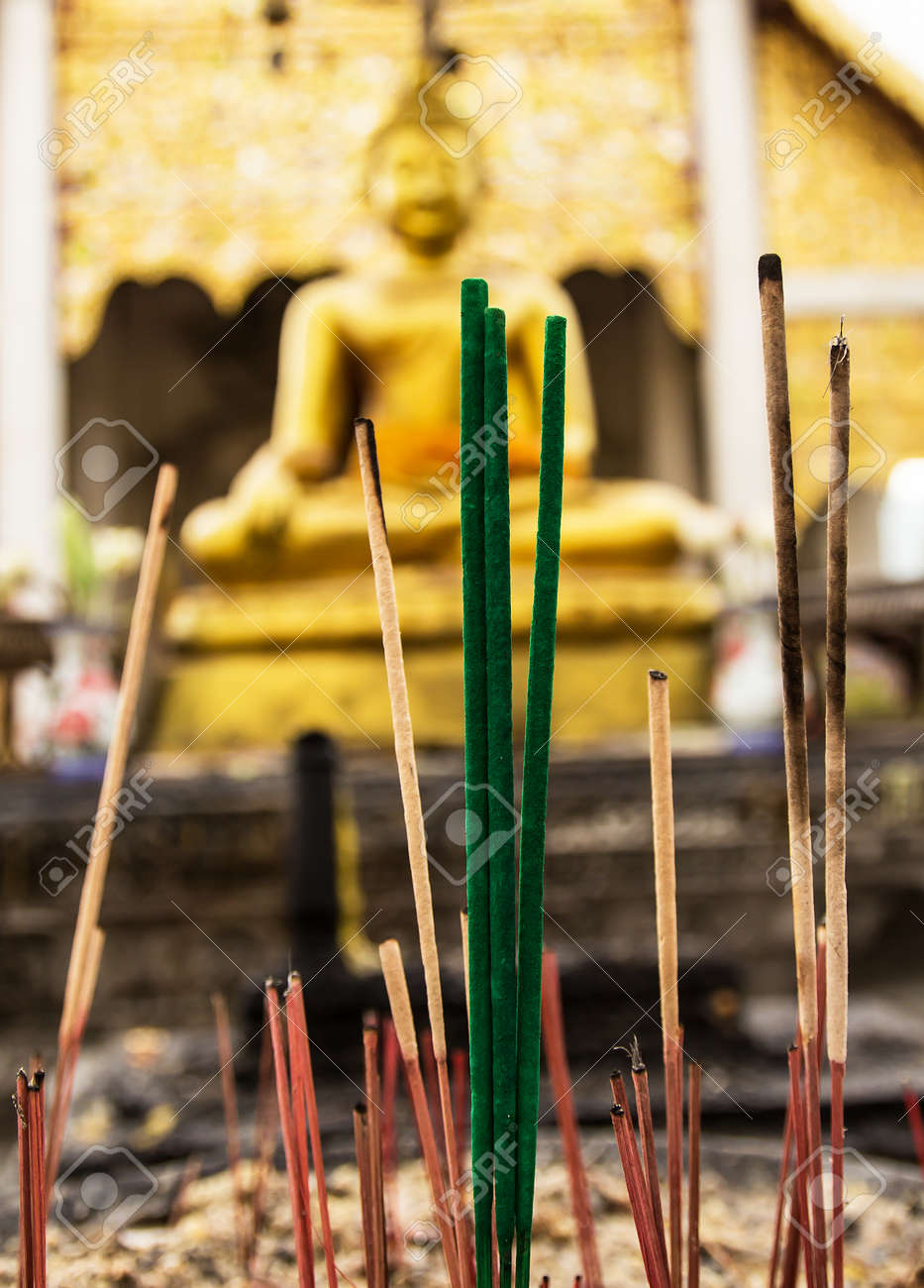 Burned incense sticks in the Incense holder and buddha statues are blackground Stock Photo - 25245307