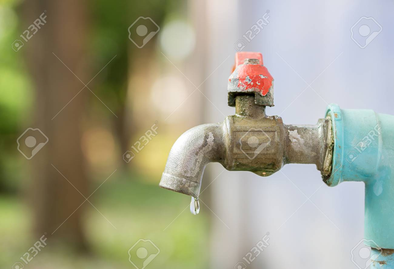 Close Up To Faucet Water In The Garden With Blur Background