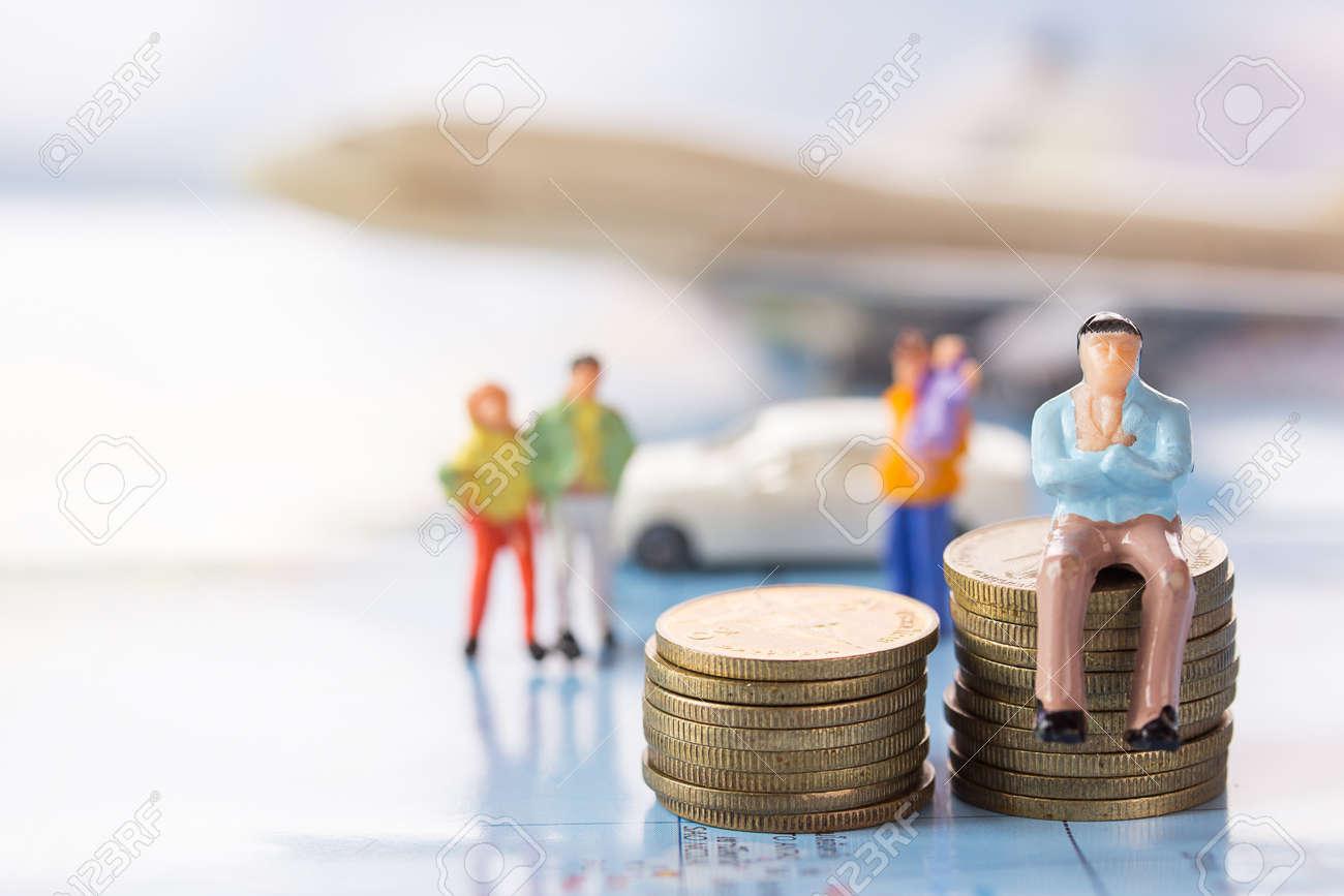 ミニチュアの人々 実業家数字車と飛行機の背景をぼかした写真をコインの上に座って お金と金融の概念 事業の背景や壁紙として使用するための領域をコピーします の写真素材 画像素材 Image