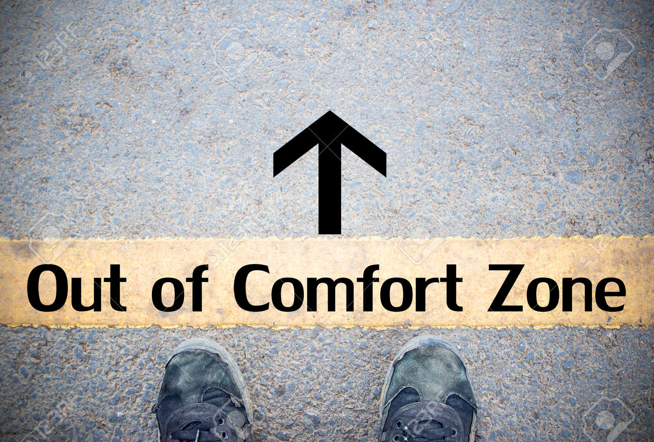 Male feet and old black shoes standing on the concrete floor or street asphalt pavement with dividing line. Space for text and design and Comfort Zone Concept - 100602660
