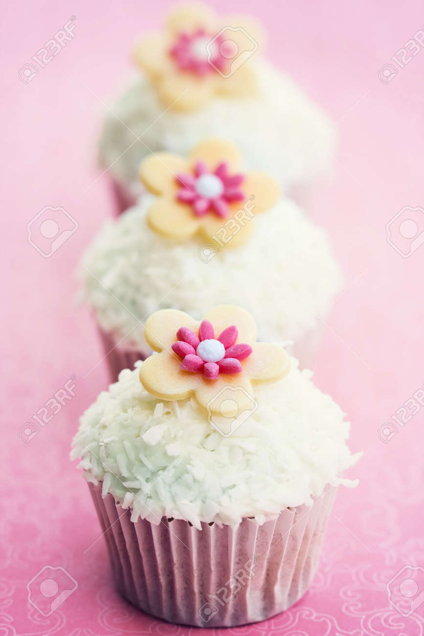 Cupcakes decorated with dessicated coconut and sugar flowers Stock Photo - 7111587
