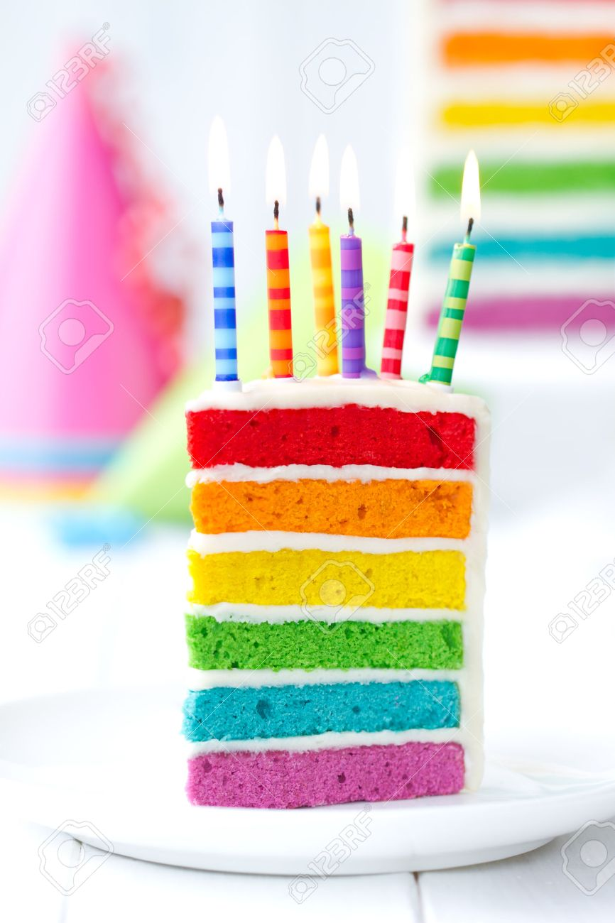Rainbow Cake Decorated With Birthday Candles Stock Photo