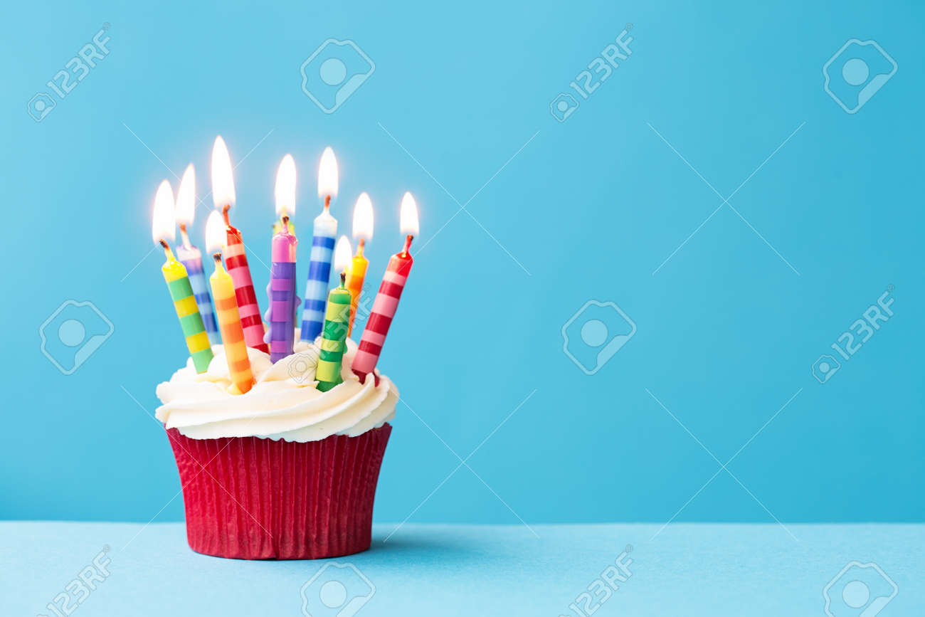 Birthday Cupcake Against A Blue Background Stock Photo Picture And