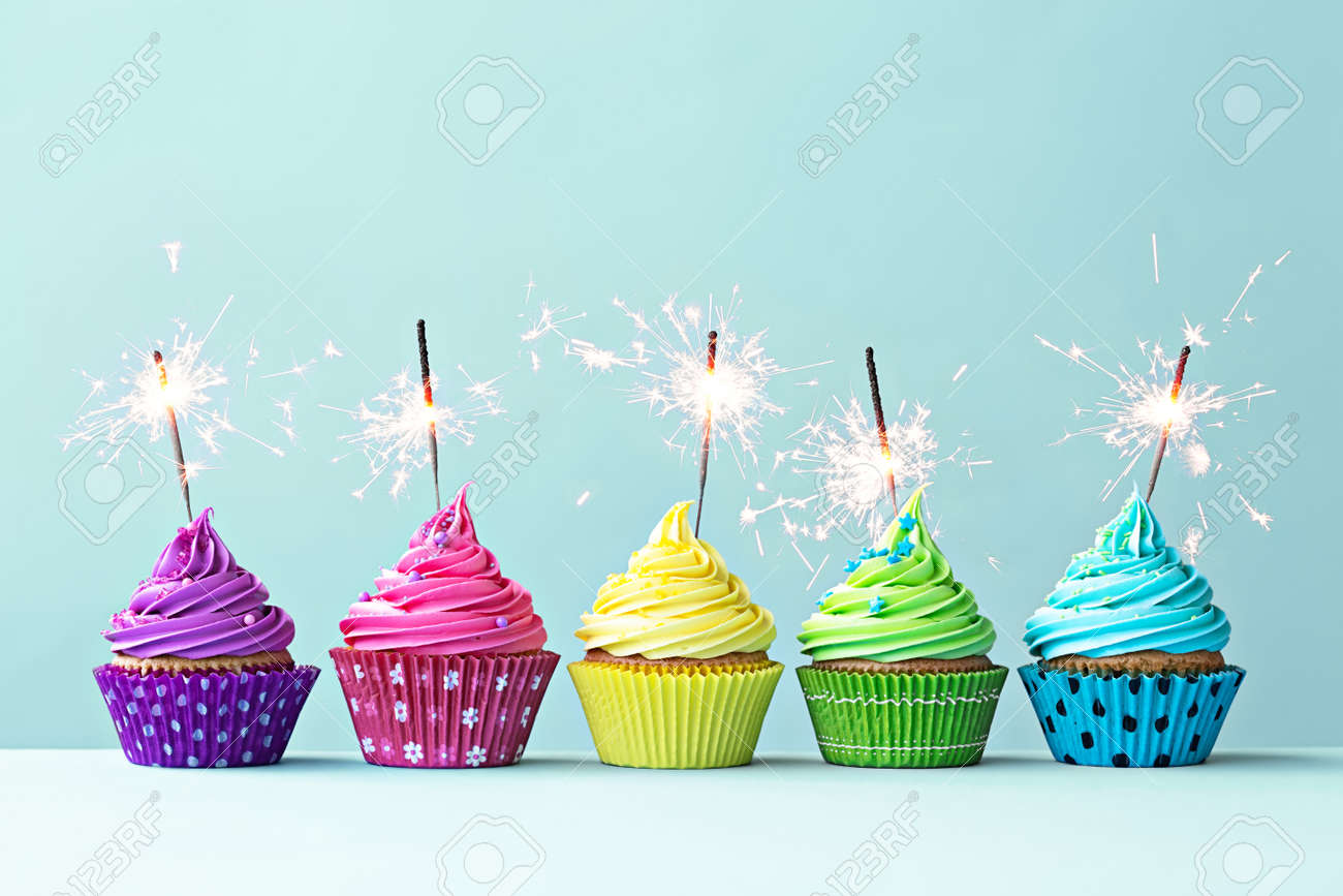 Row of colorful cupcakes with sparklers Stock Photo - 35959693