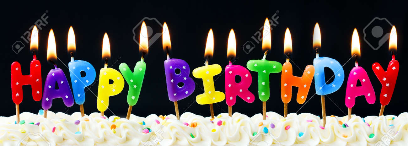 Happy Birthday Candles Against A Black Background Stock Photo