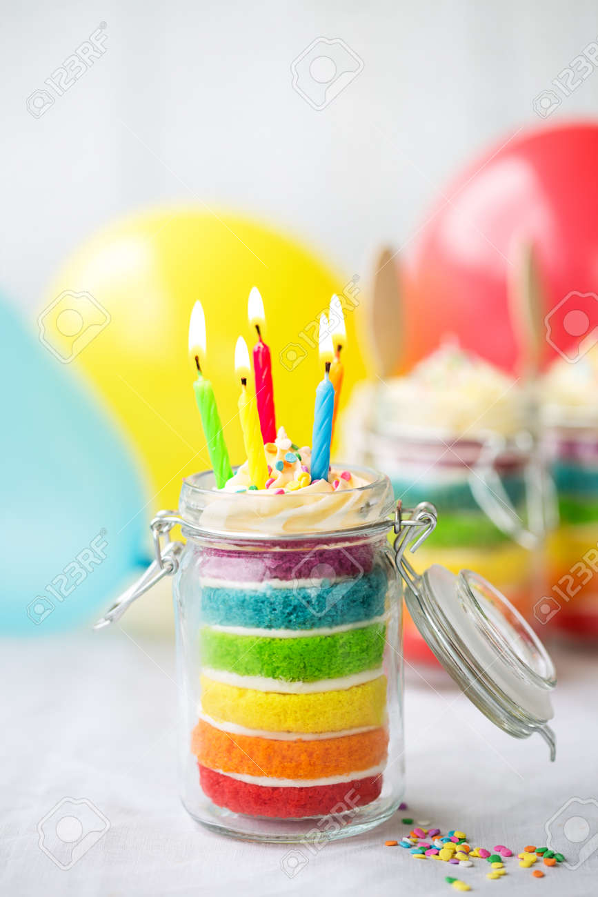 Rainbow Layer Cake In A Jar With Birthday Candles Stock Photo