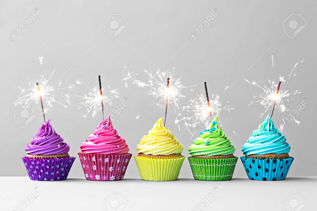 Row of colorful cupcakes with sparklers - 51187451