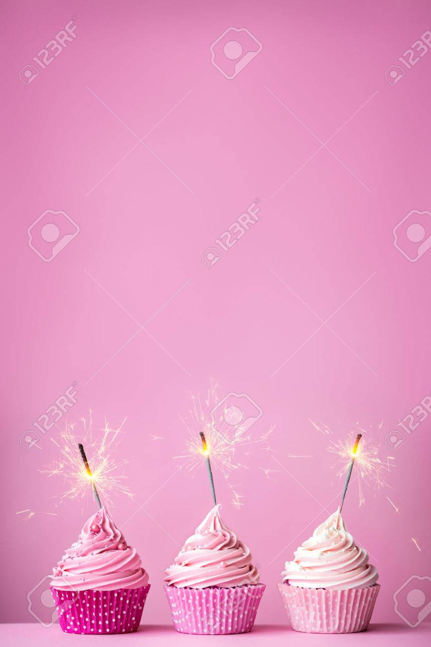 Pink cupcakes with sparklers and copy space above - 52676802