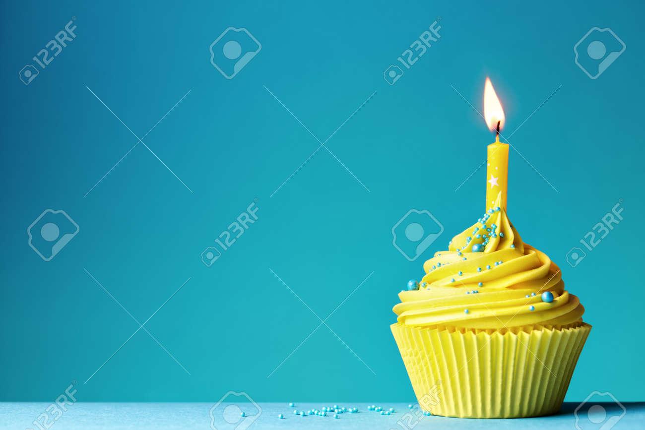 Yellow birthday cupcake on blue - 53446827