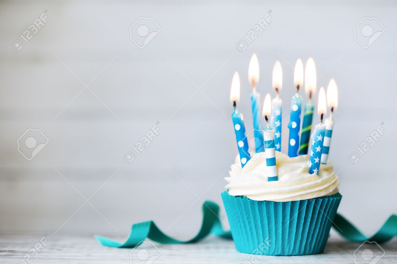 Cupcake with blue birthday candles - 56383341