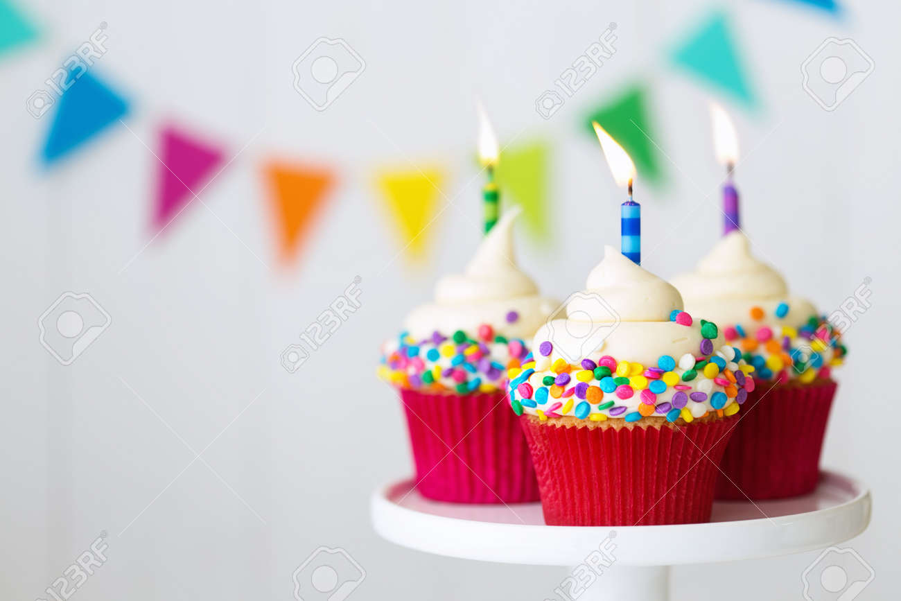 Colorful birthday cupcakes on a cake stand - 57319533