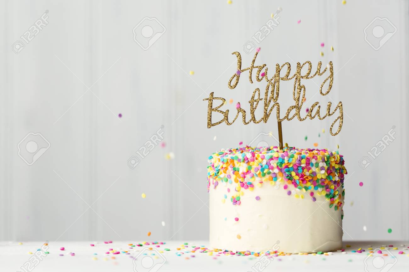 Colorful Birthday Cake With Golden Happy Banner And Falling Sprinkles Stock Photo