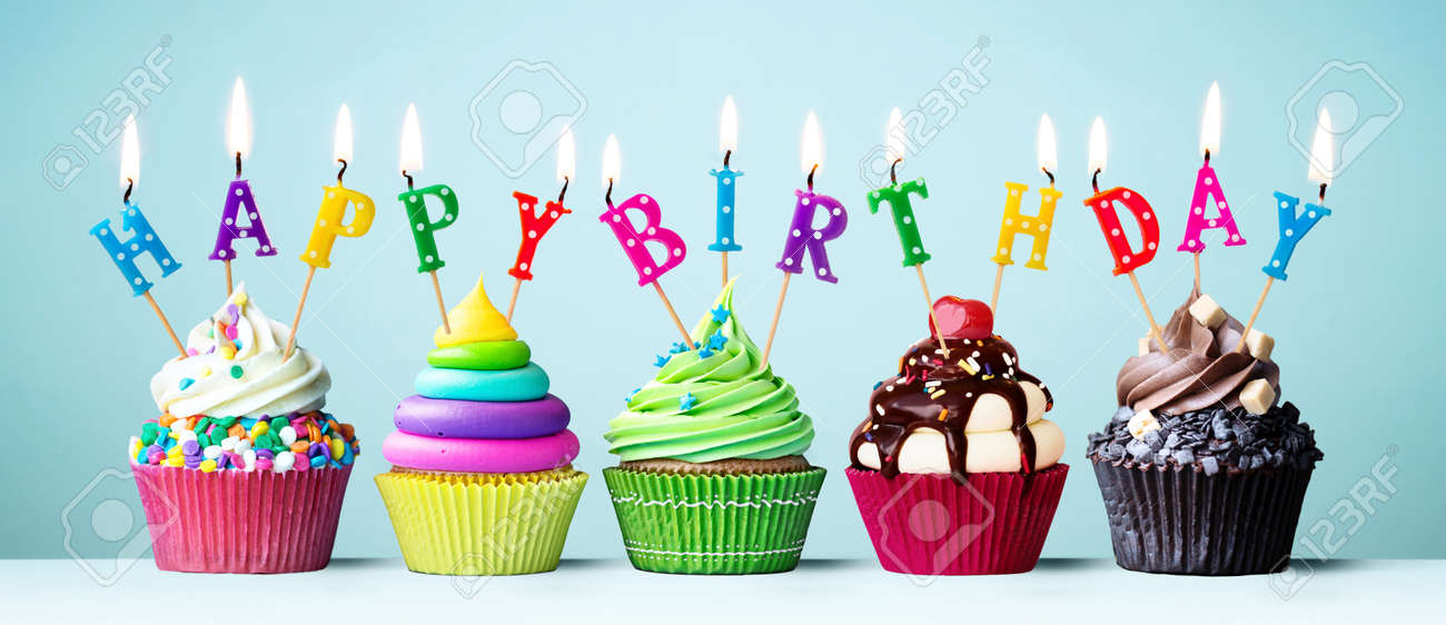 Colorful cupcakes with candles spelling Happy Birthday - 123199734