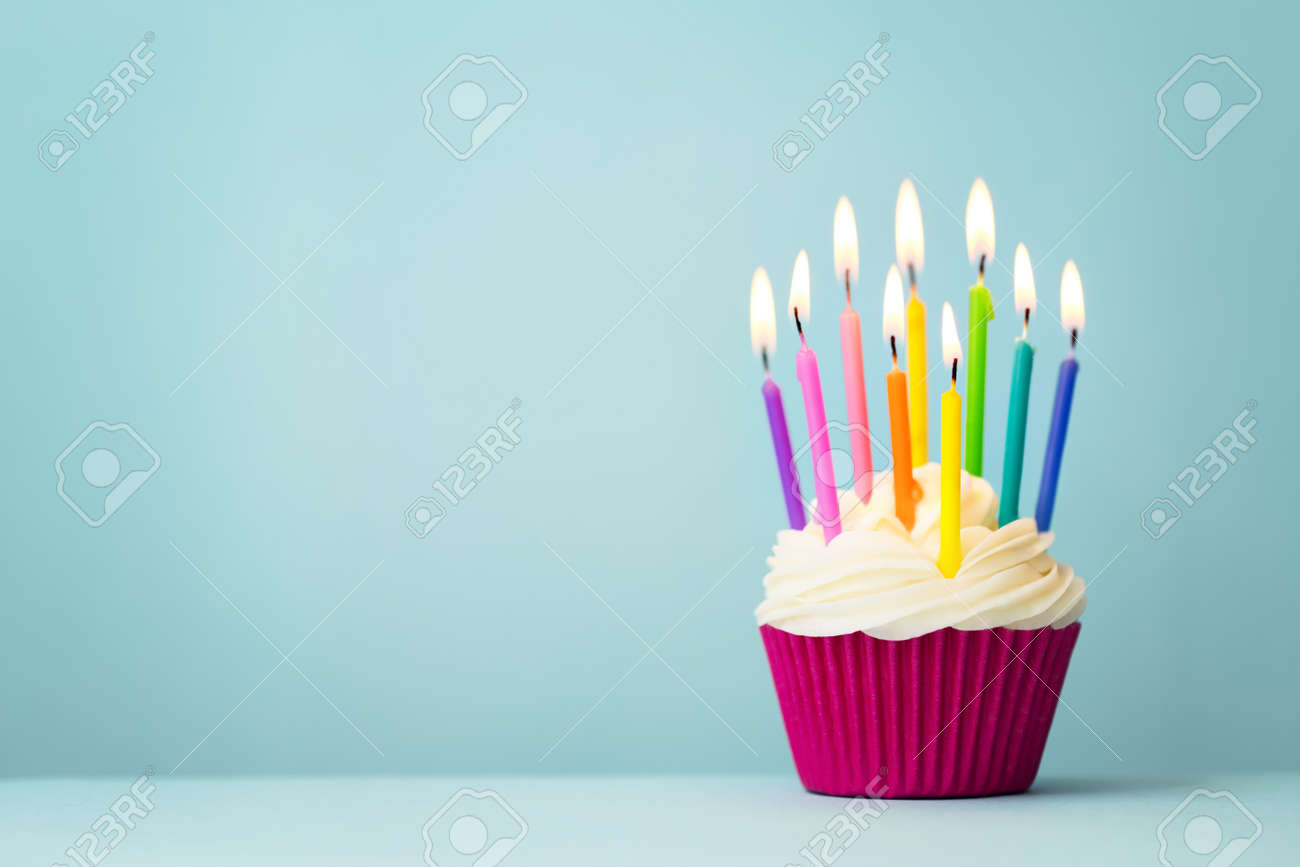 Birthday cupcake with rainbow colored candles - 144906236
