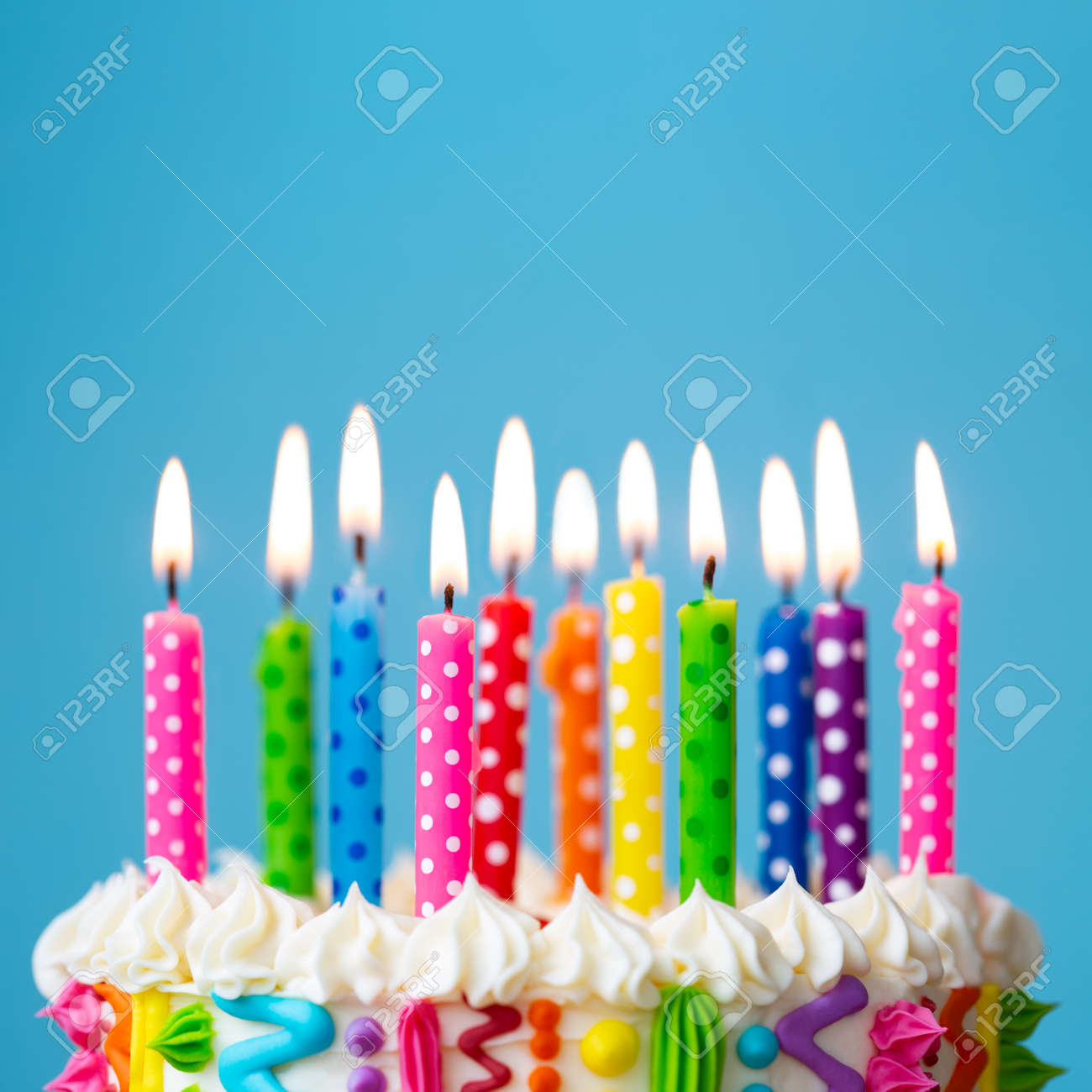 Colorful birthday cake with rainbow colored candles - 169034812