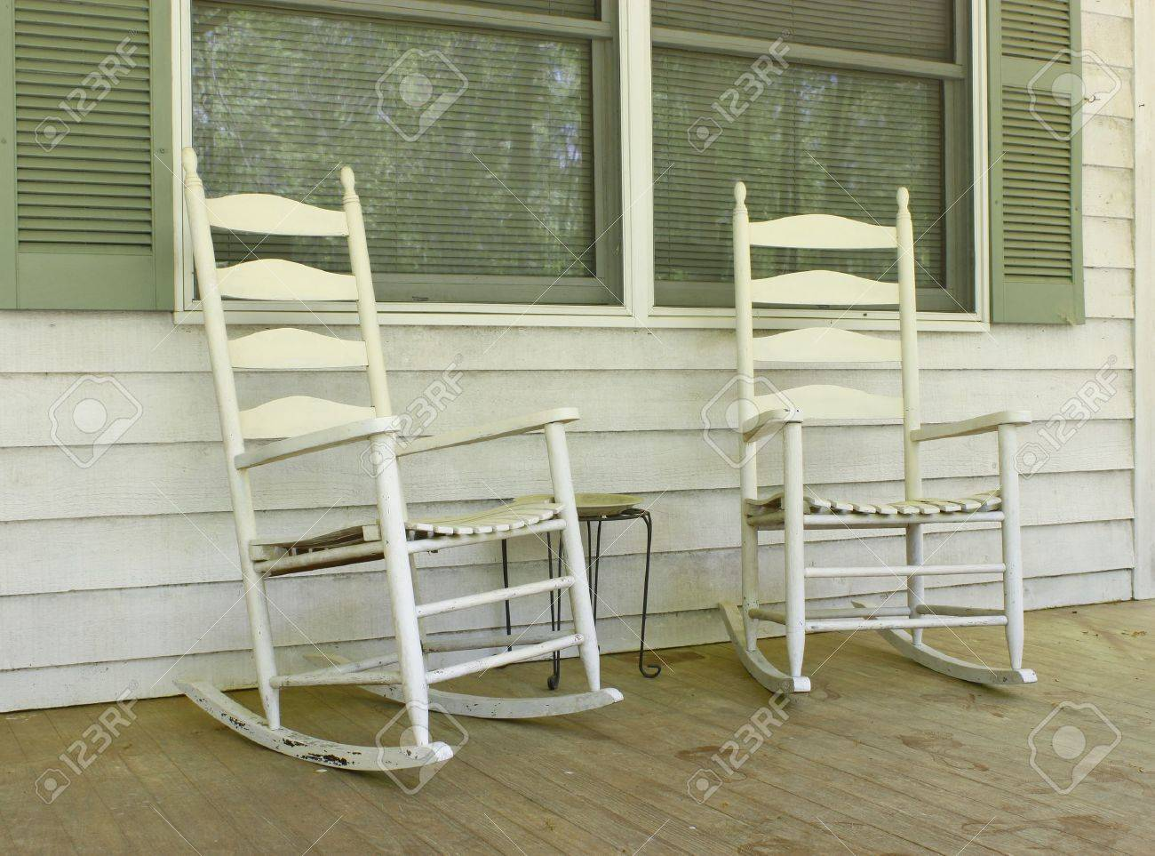 two old white painted wooden rocking chairs on a front porch stock