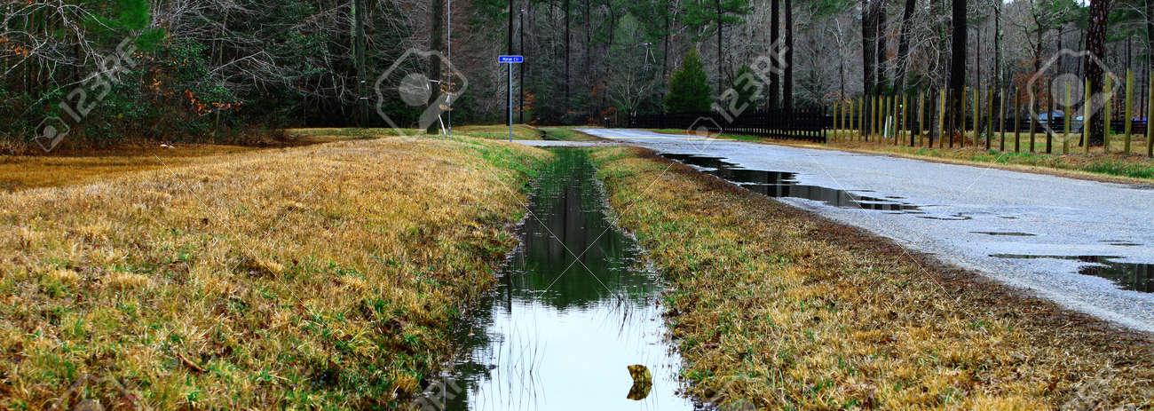 Ein Graben Voll Wasser Abfluss Entlang Einer Straße Und Zaun In Einer  Ländlichen Umgebung Standard