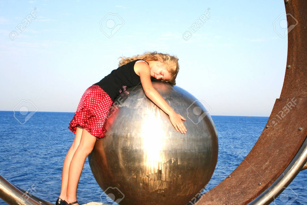 Blond girl on the metallic ball. Stock Photo - 4634573