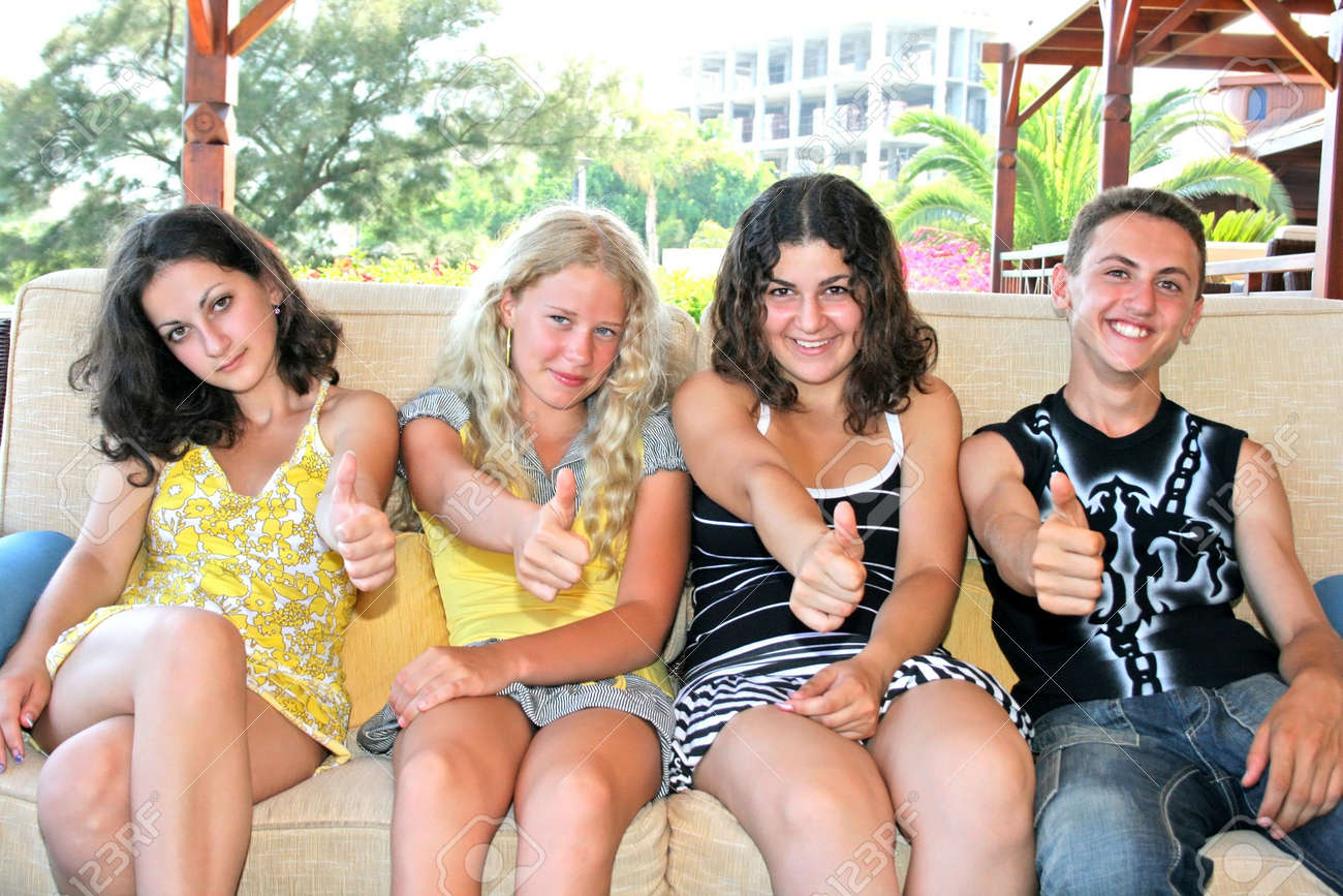 Pretty blond and brunette girls and boy having fun on the sofa. Stock Photo - 4653077
