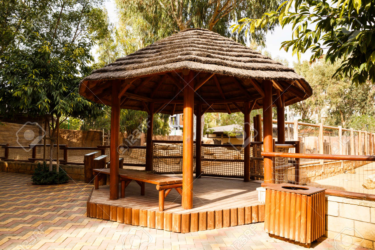Wooden round pavillion with bench in the park