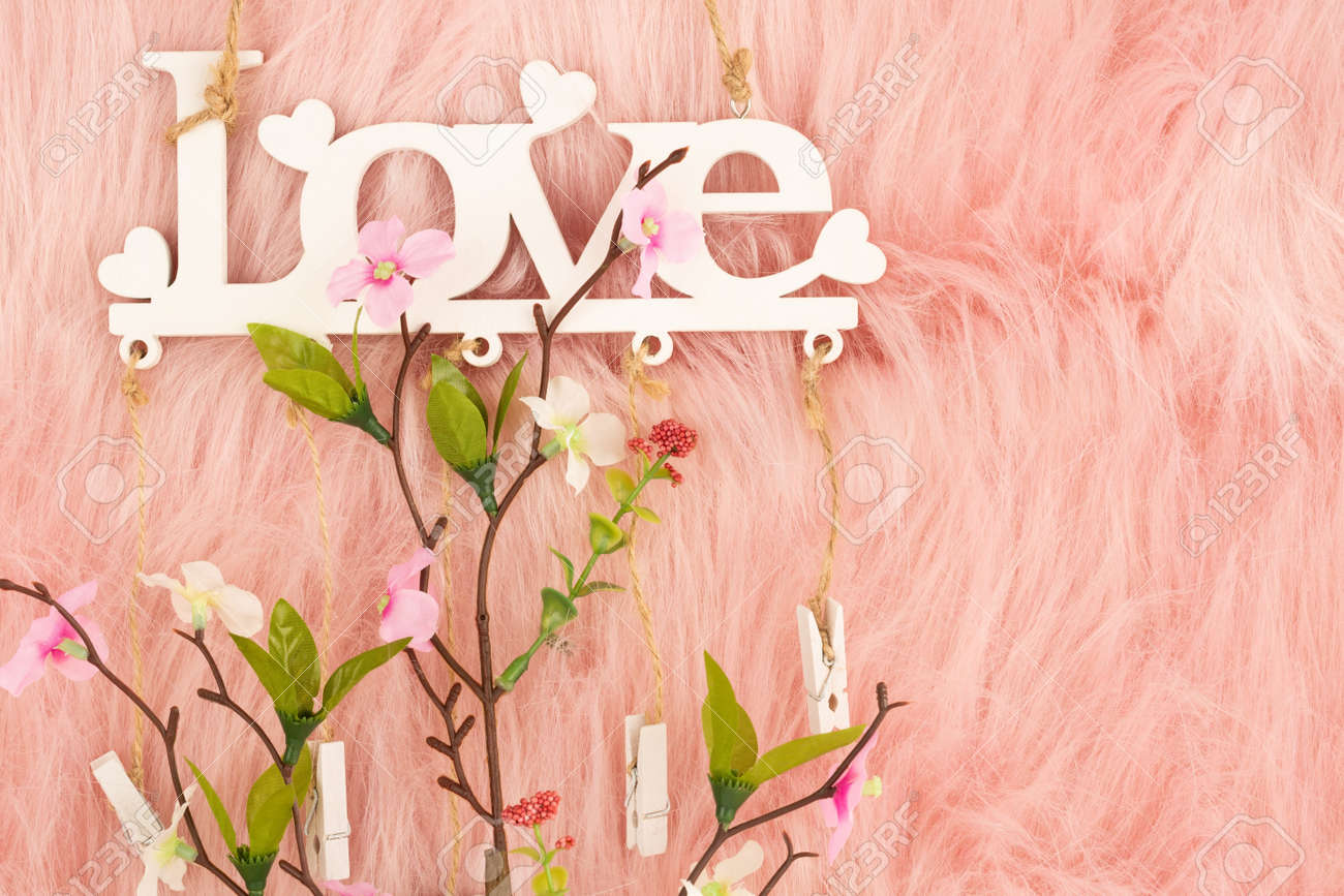 White wooden word love and flowers on pink fur background. - 136731619