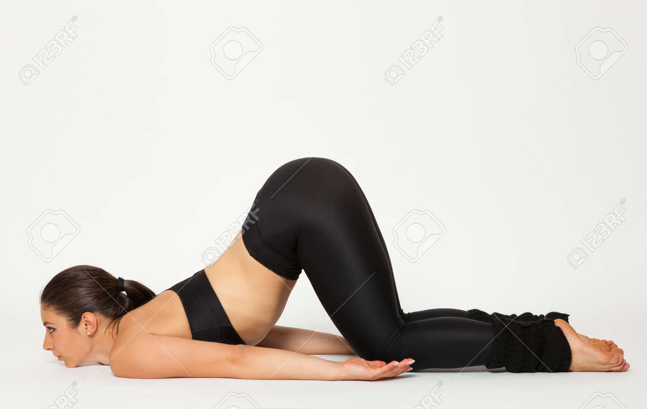 Sexy fit brunette woman in sportswear doing yoga exercises. Studio shot.  White background Stock