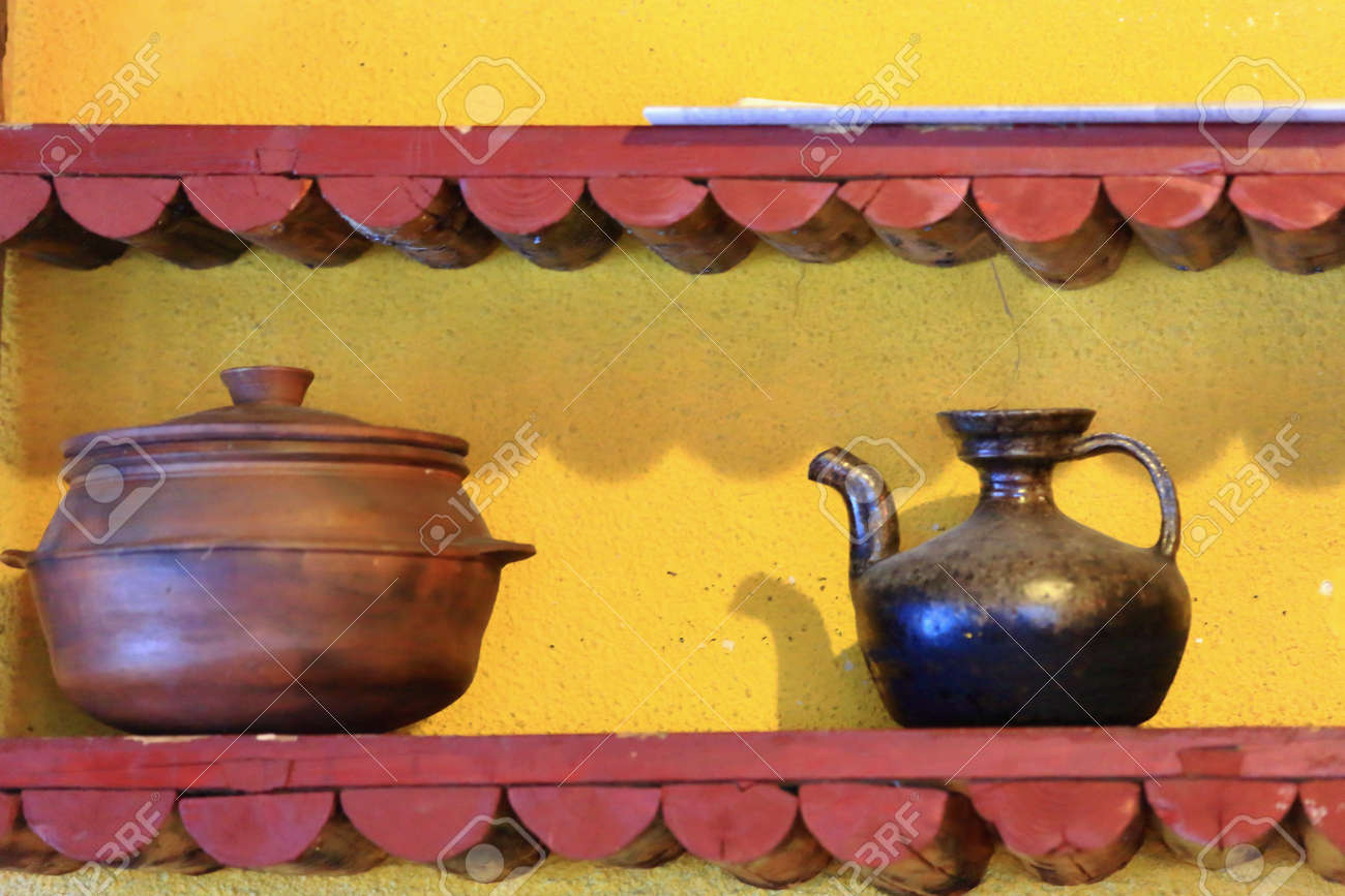 Old Teapot And Copper Vessel Set On Red Wooden Shelf On The Yellow ...
