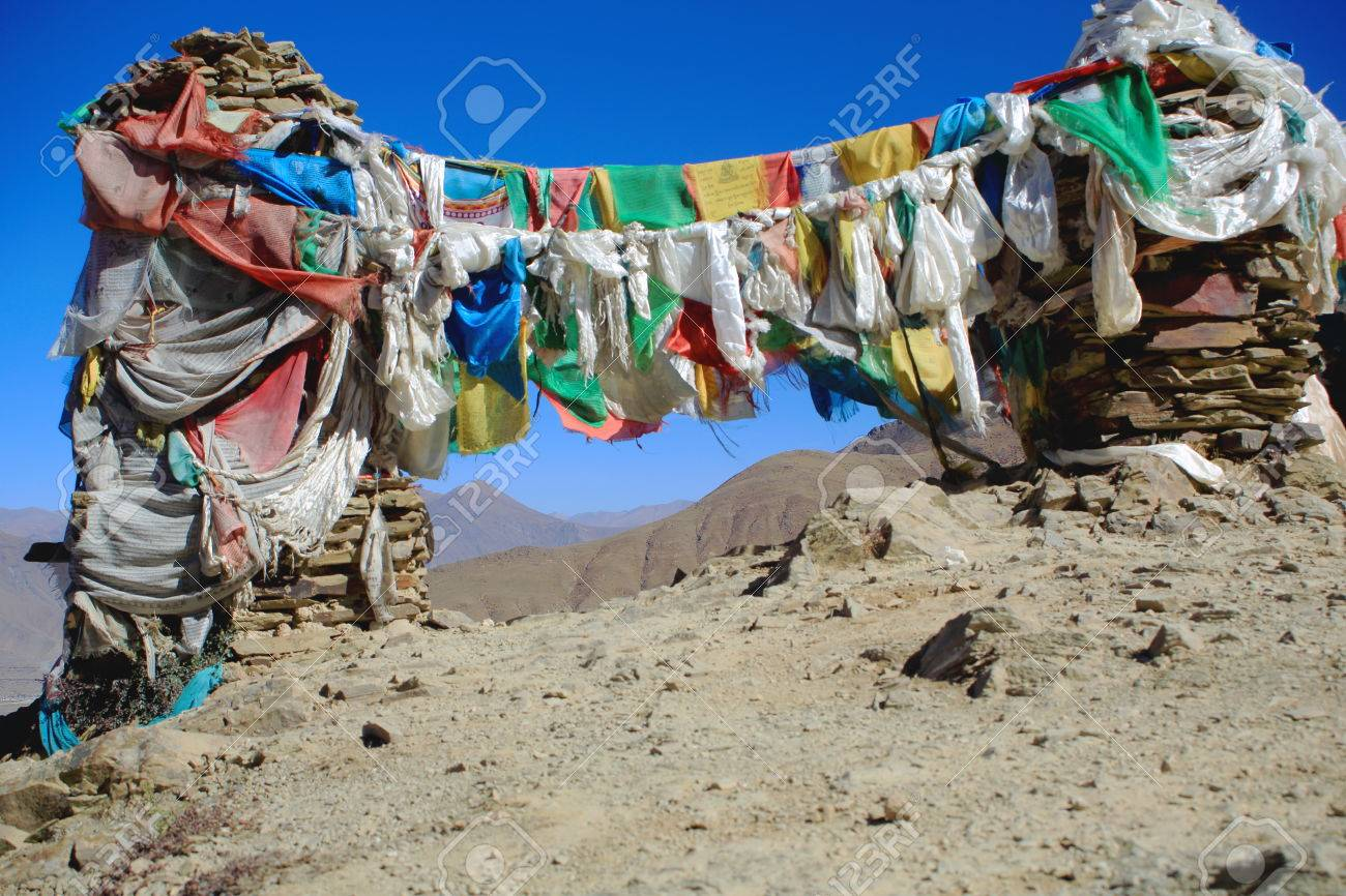 Five colored buddhist prayer flags hanging from cairns-stacked