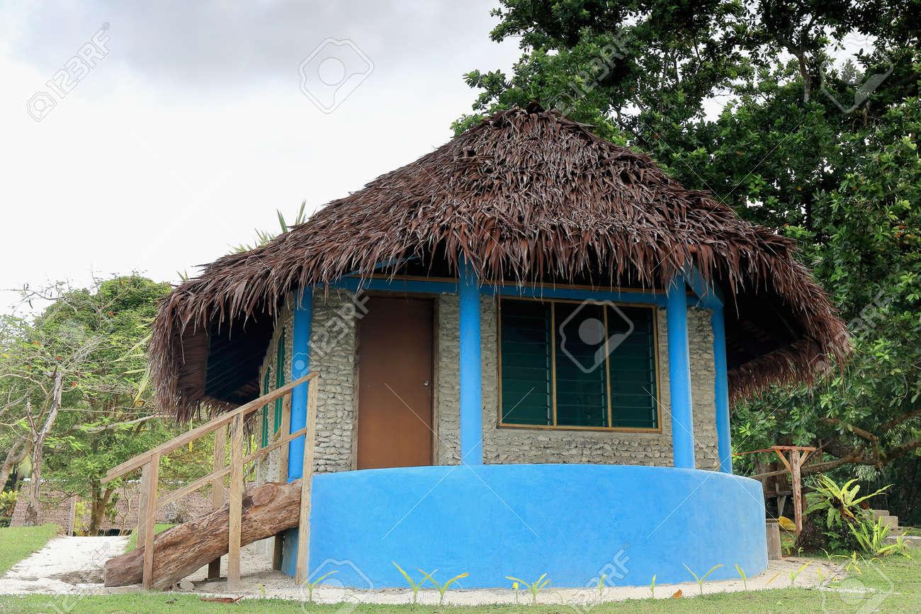 Bleu peint bungalow au toit de chaume avec véranda et maçonnerie mur de  pierre de corail dans le feuillage tropical de Lonnoc Beach. village Hog ...
