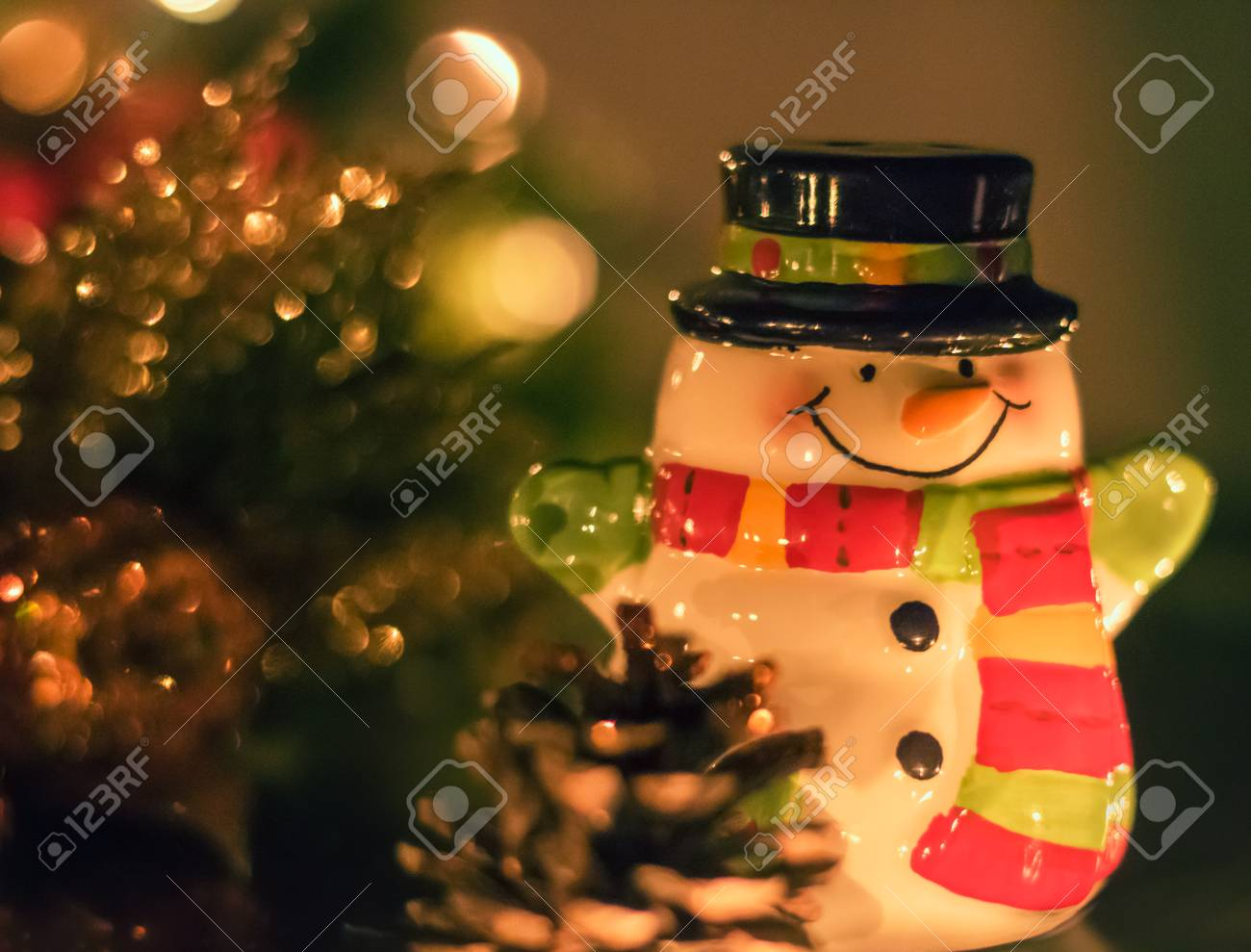 6c252699667 A tiny ceramic snowman suited up with a scarf and black top hat is standing  with