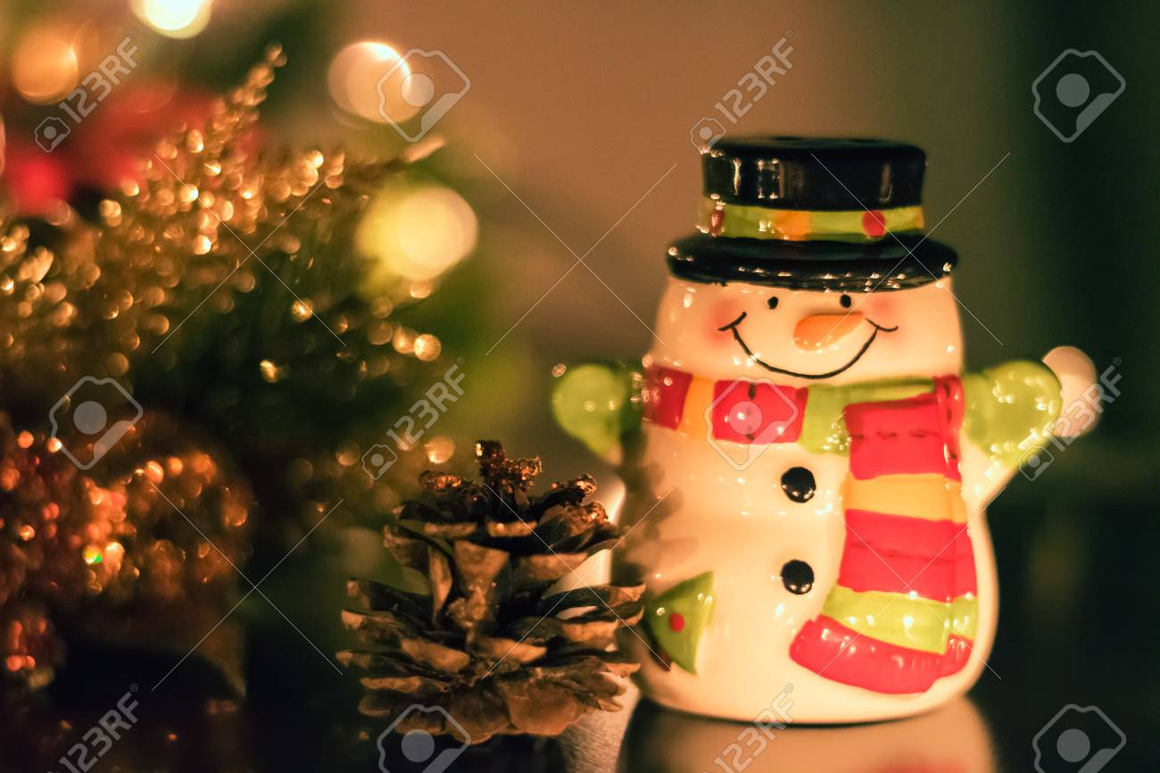 A Tiny Ceramic Snowman Suited Up With A Scarf And Black Top Hat
