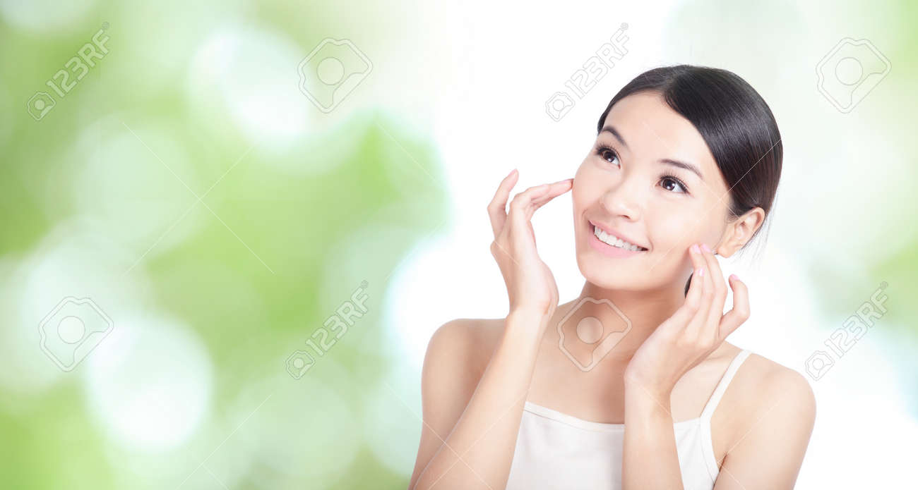 Young woman smile and hand touch face look to up forward concept for health body care with green nature background, model is a asian beauty Standard-Bild - 13547220