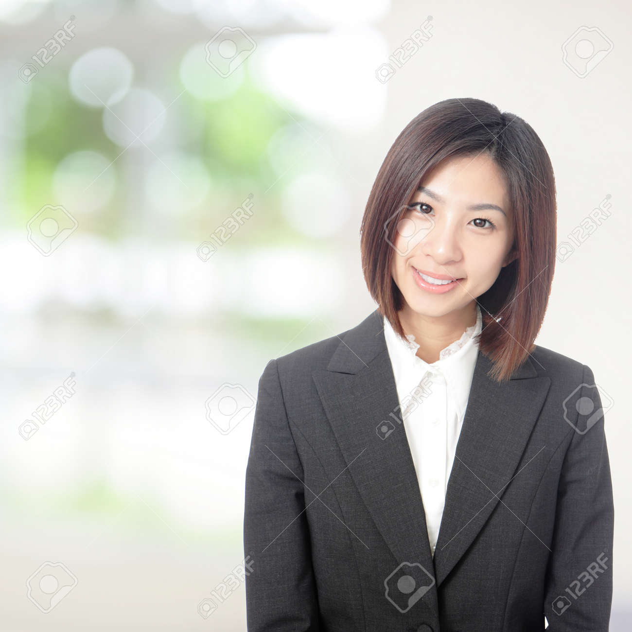 Young beautiful business woman smile portrait with nature green background, model is a asian beauty Stock Photo - 14101169