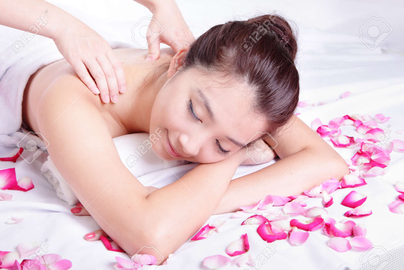 Beautiful woman smile getting massage and spa treatment with rose background, model is a asian beauty Stock Photo - 14174388