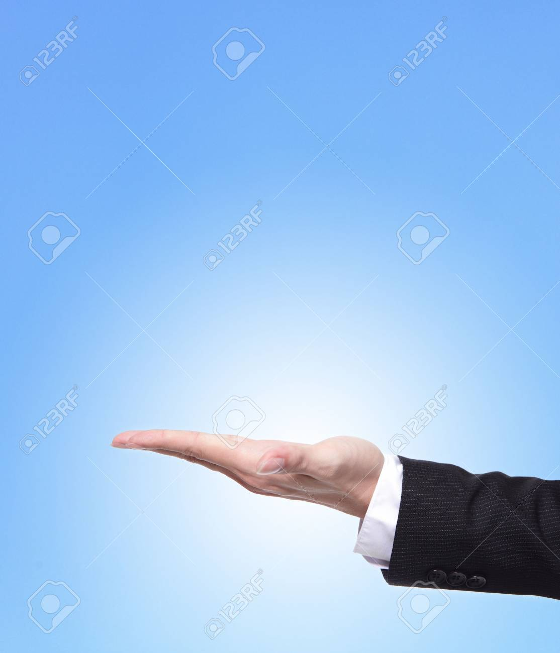 Business man holding something on his hand close up isolated on blue background, copy space area in the image is great for you Stock Photo - 16987958