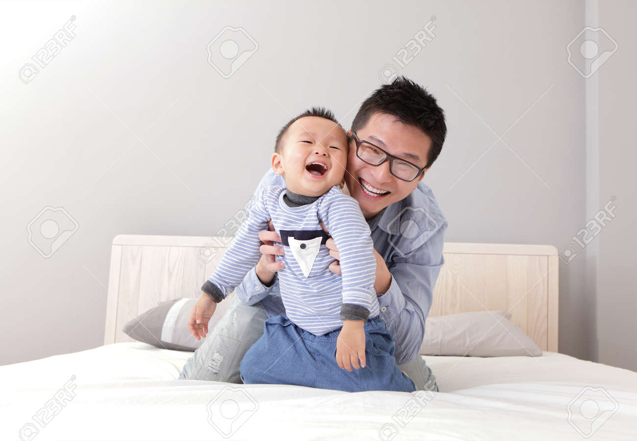 young father play with his son boy on the bed at home, asian lifestyle Stock Photo - 17542018