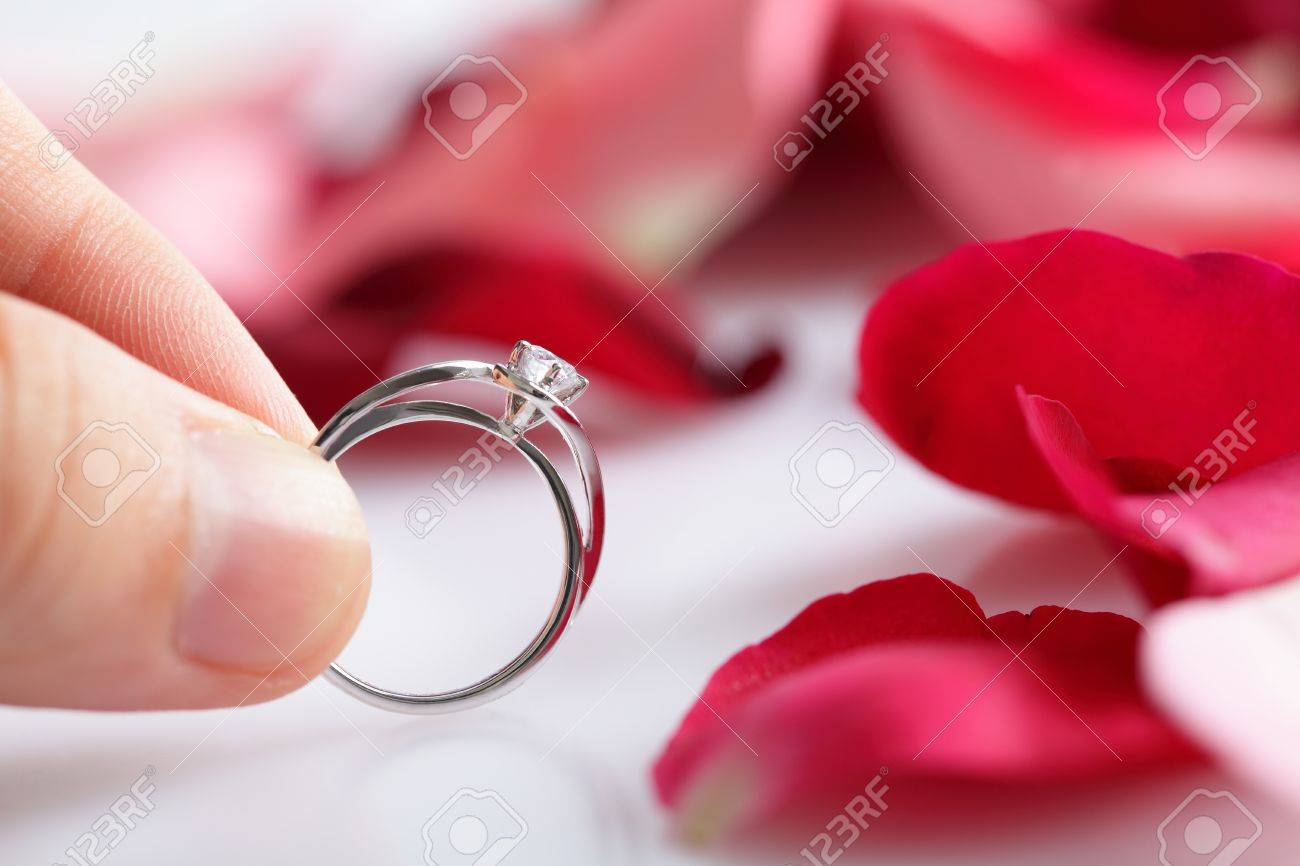 76e11781c9cf married couple holding diamond ring over roses flowers petal Stock Photo -  18403743