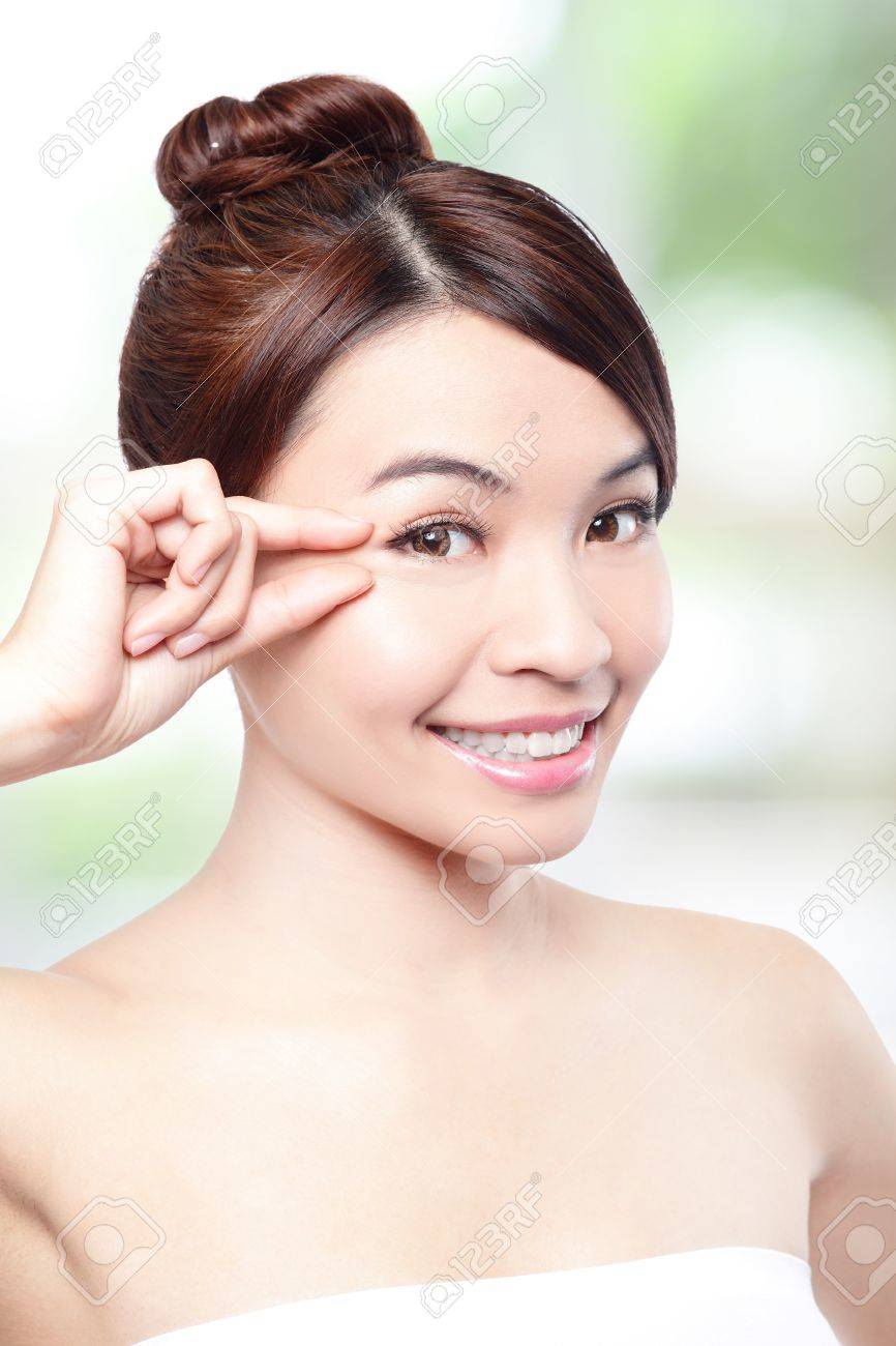 Beautiful woman smile face and finger touch her eyes with clean face skin, concept for eye and skin care, over nature green background, asian beauty Stock Photo - 19364136
