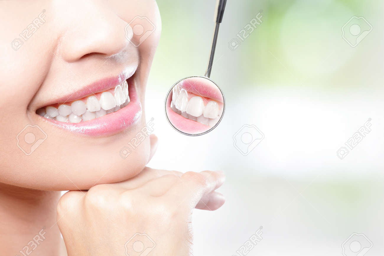 Healthy woman teeth and a dentist mouth mirror with nature green background Stock Photo - 20481718