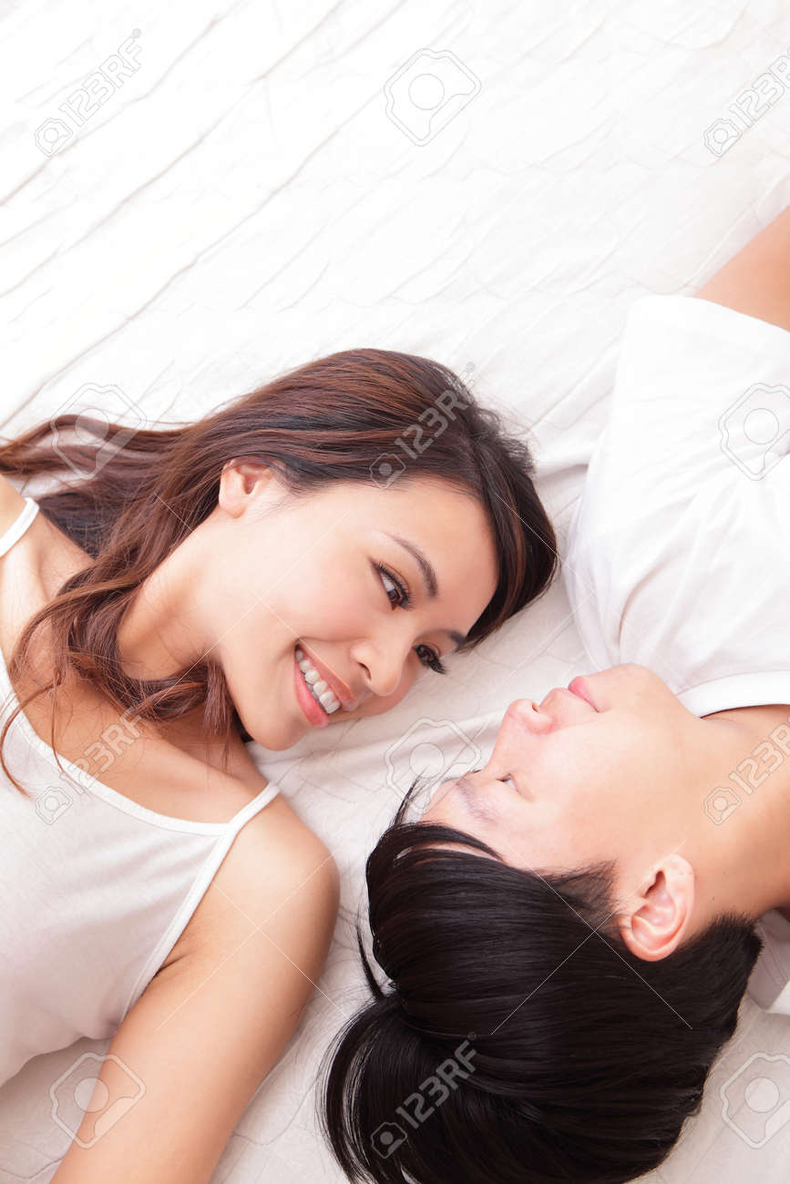 young lovely couple lying in a bed, happy smile looking to each other, top view, asian people Stock Photo - 21171118