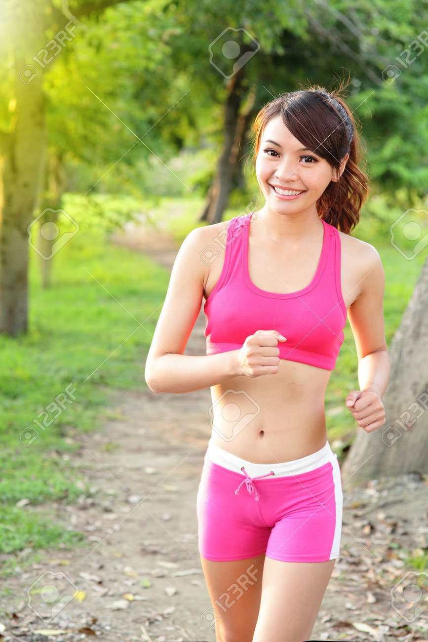 f582925983099 Running woman in park. Asian sport fitness model in sporty running clothes.  Stock Photo