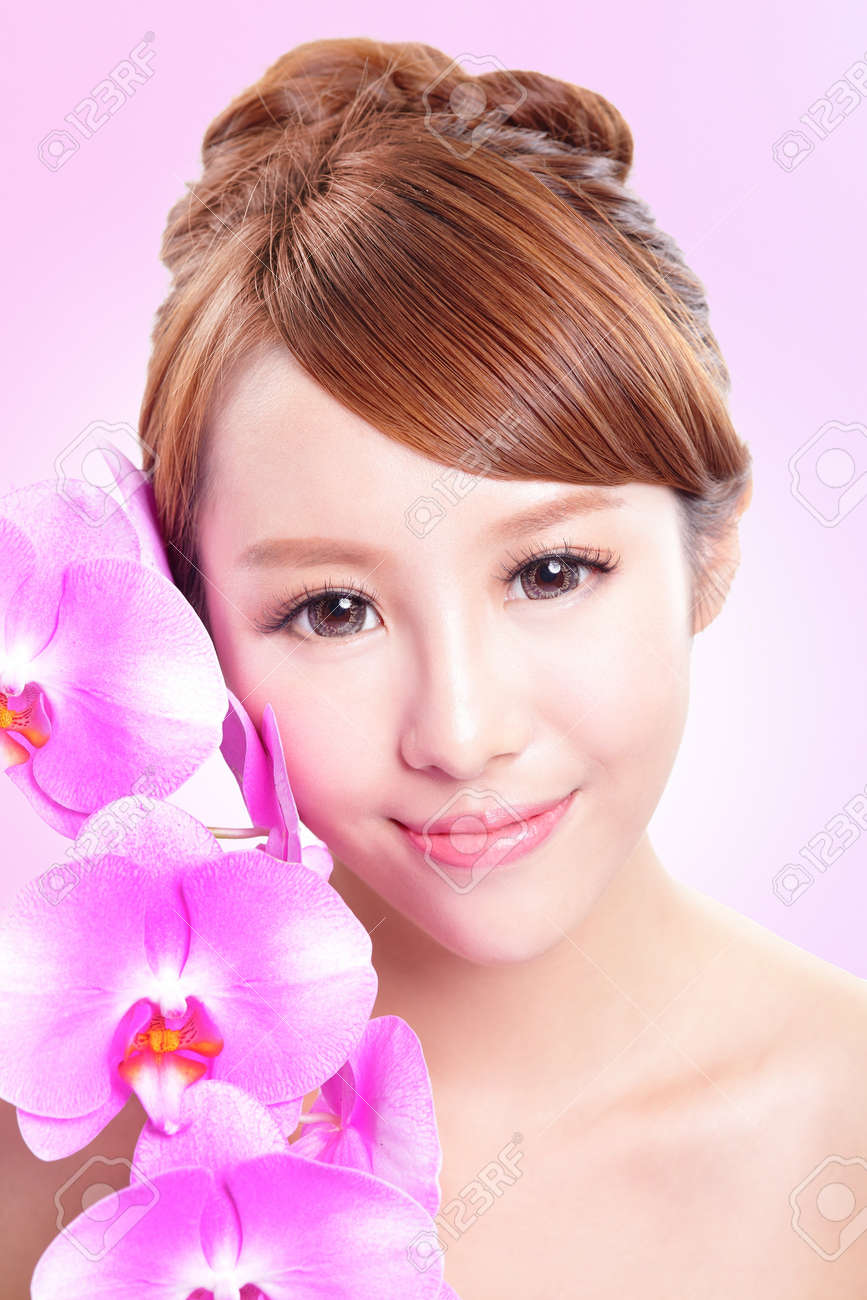 Beautiful woman smile face with orchid flowers and health skin isolated on pink background, asian model Stock Photo - 21378586
