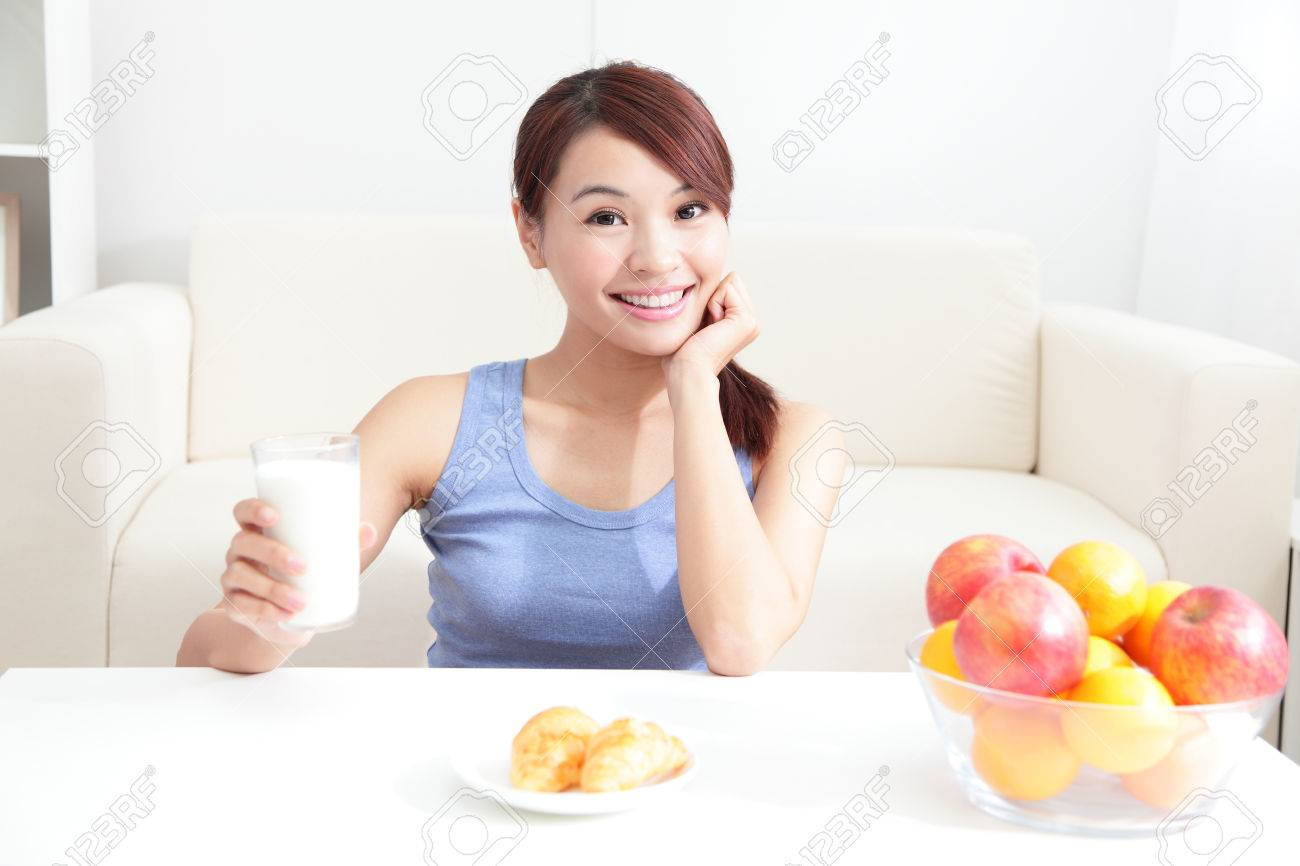 Cheerful woman drinking milk sitting on her sofa at home, asian beauty Stock Photo - 22851670